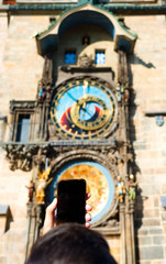 young man taking a picture of the Prague clock
