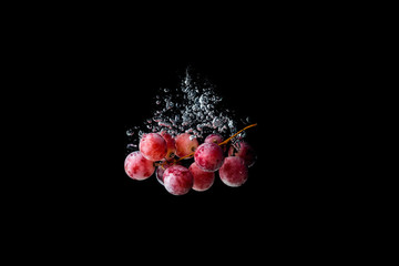 Red grapes sinking in water on black background with air bubbles.