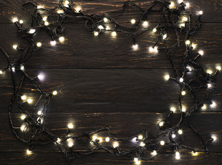 Frame of christmas garland lights on wooden background