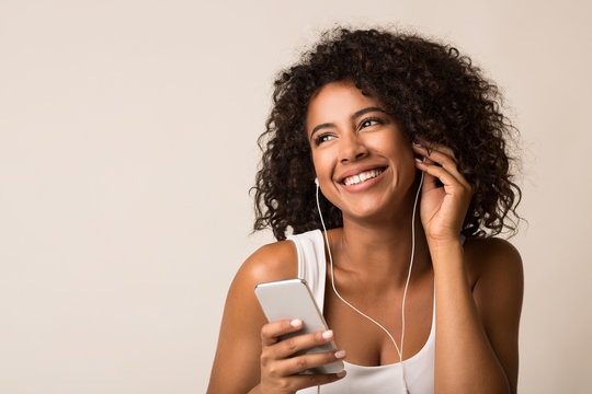 Smiling african-american woman in earbuds listening music