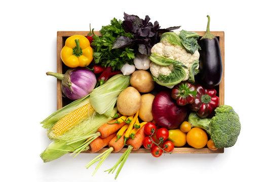 Fresh organic vegetables in wooden box on white