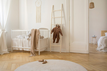 Round white carpet on the wooden floor of stylish scandinavian nursery, real photo