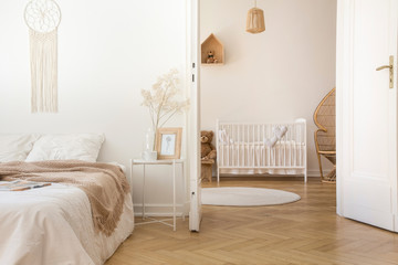 White scandinavian bedroom with door open to nursery with crib and toys, real photo