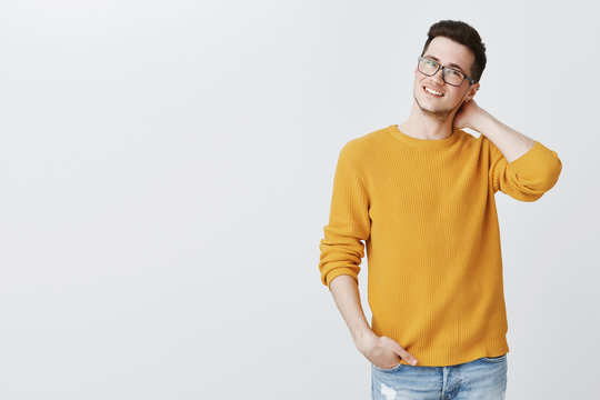 Indoor shot of charming nice and handsome young guy in glasses and yellow sweater touching back of neck shy and unsure holding hand in pocket, smiling as trying ask girl out for date