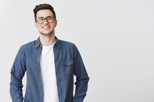 Waist-up shot of happy friendly-looking handsome young smart male coworker in glasses and blue shirt smiling standing over gray background proud and satisfied, grinning at camera from joy