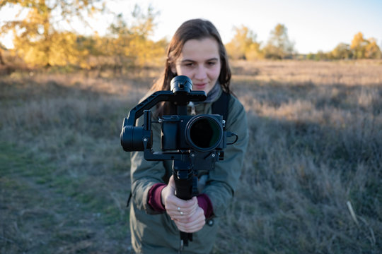 Female videographer holding a gimbal with mirrorless camera. Woman with stabilized camera rig filming outdoors on a sunny afternoon