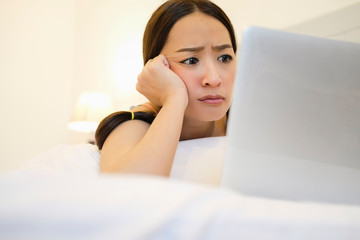 pretty woman in emotional sad by reading news in laptop on bed