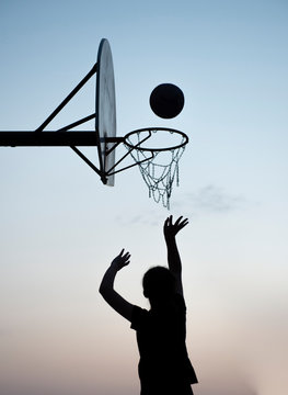 Silhouette of a young girl shooting a basketball