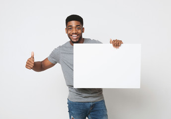 Fototapeta African-american man holding white blank board and showing thumb up obraz