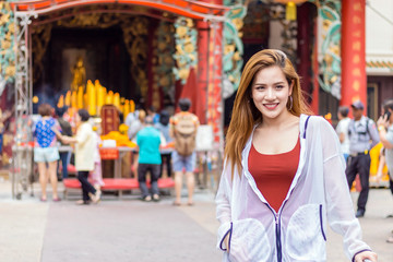 A woman standing in front of a shrine at Chinatown, Yaowarat, Bangkok, Thailand.