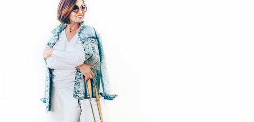 Wall Mural - Woman in elegant outfit with oversize denim jacket. City street fashion