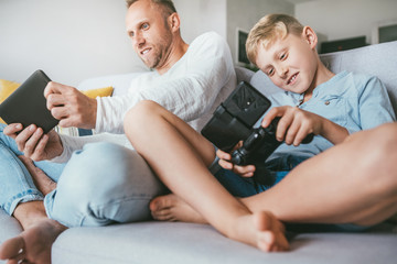 Father and son emotionally playing with electronic devices: tablet and gamepad sitting in living room