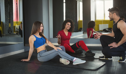 Personal trainer and young sports girls sitting on floor