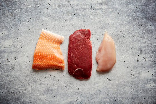 Three pieces of different kinds of raw meat. Chicken brest, beef steak and salmon fillet. Top view on gray stone background.