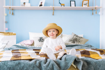 Smiling little baby girl in straw hat sitting in bed at home