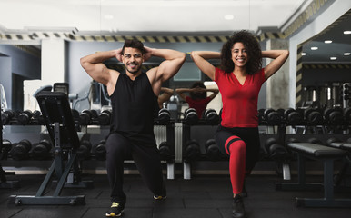 Diverse sporty couple working out in gym together Wall mural