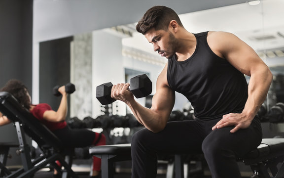 Arab muscular man doing biceps workouts in gym