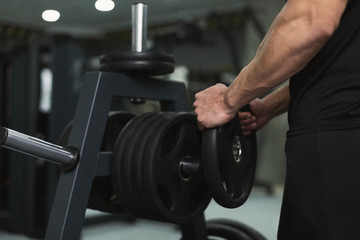 Muscular man bodybuilder picking up heavy dumbbell
