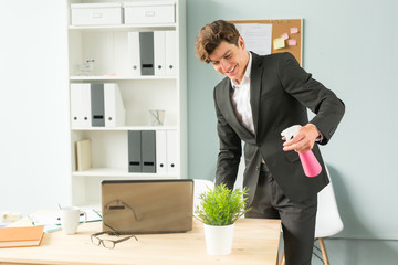 Business people, fun and potted plants concept - young funny businessman watering plant at office