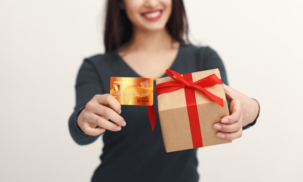 Beautiful woman holding credit card and gift box