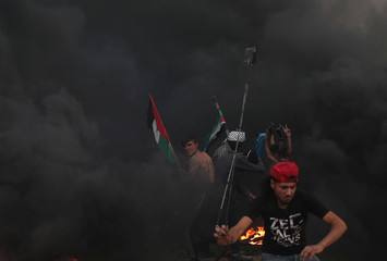 Palestinian demonstrators react during a protest at the Israel-Gaza border fence in Gaza