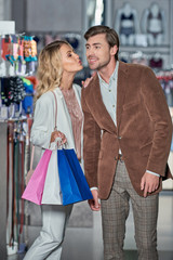 happy woman holding shopping bags and kissing smiling man in shop