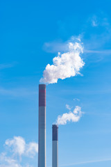 smoking chimney against blue sky
