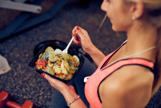 Top view of woman eating healthy food while sitting in a gym. Heatlhy lifestyle concept.