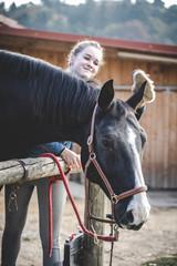 Fototapeta Junge schöne Frau und schwarzes Pferd Ausritt, reiten, Derssur, Reiterin