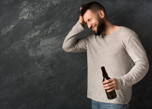 Young guy with headache holding bottle of beer