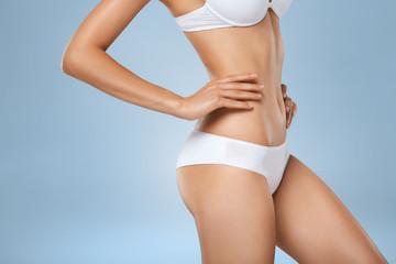 Unrecognizable slim tanned woman body in underwear