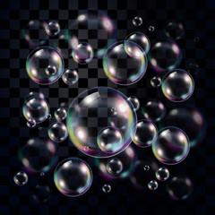 Transparent and multicolored soap bubbles over dark