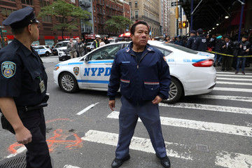 A postal employee stands on the street after a suspicious package was discovered at a U.S. Postal Service facility in the Manhattan borough of New York