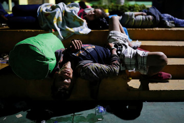 Central American migrants, part of a caravan trying to reach the U.S., sleep in a public square as they wait to regroup with more migrants, in Tecun Uman
