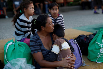 Maria Nino, migrant from Honduras and part of a caravan trying to reach the U.S., holds her son Marvin after they spent the night in a public square, in Tecun Uman