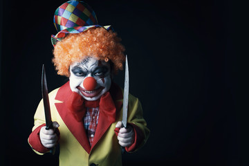 Halloween. Scary clown with knives.