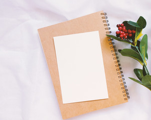 Flat lay style of blank card on notebook with flowers decorated on white cloth, top view