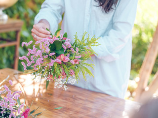 Crop woman arranging flowers in garden