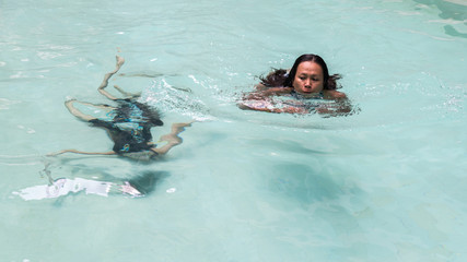 Mother and daughter swimming in pool