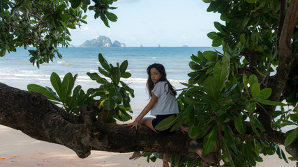 teenager sitting on tree at beach