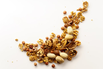 Overhead image of a group of various nuts with nutshells isolated on white background with copy space