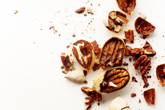 Cracked and opened pecan nuts and nuts in shell. Overhead wiew on white background with copy space