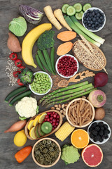 Healthy high fibre food concept with fruit, vegetables, grain, whole wheat pasta and seeds. High in antioxidants, anthocyanins, vitamins and minerals. Top view on marble background.