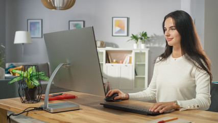 Portrait Shot of the Beautiful Young Woman Working on Personal Computer from Her Cozy Living Room. She Smiles Charmingly.