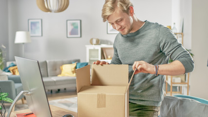 Handsome Young Man in Living Room Opening Cardboard Box Package With Interest.