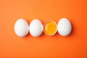 Raw chicken eggs on color background, top view