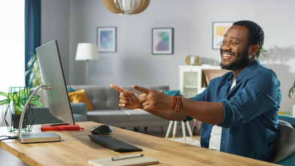 Portrait of the Handsome African American Man Pointing at the Screen with Two Fingers while Sitting at His Workplace. Young Man Having Fun at Home.