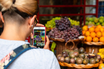 Phone in the hand of a girl with a photo of fruit. Selective focus.