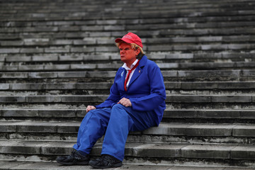 An attendee, dressed as U.S.A. President Donald Trump, sits on stairs as he attends the MCM London Comic Con at the Excel Centre in London