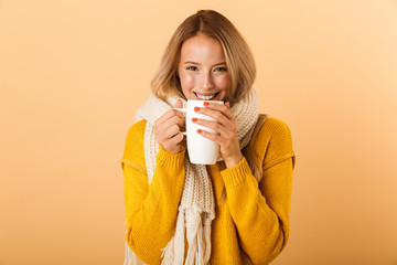 Photo sur Toile The Woman holding cup of tea wearing scarf posing isolated over yellow wall background.
